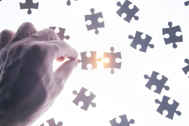 Male hand holding a jigsaw puzzle.