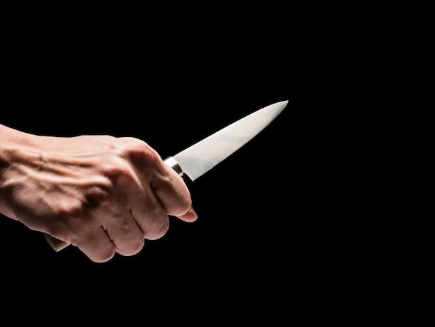검은 배경에 남자 손 잡고 칼