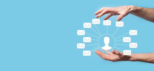 Мужская рука, держащая значок письма, значки электронной почты. свяжитесь с нами по электронной почте информационного бюллетеня и защитите свою личную информацию от спама. контактный центр обслуживания клиентов свяжитесь с нами.