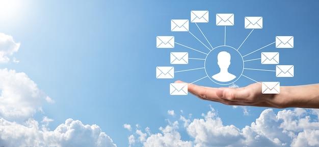 남성의 손이 편지 아이콘, 이메일 아이콘을 들고 있습니다. 뉴스레터 이메일로 문의하고 스팸 메일로부터 개인 정보를 보호하세요. 고객센터 콜센터로 연락주세요.이메일 마케팅 및 뉴스레터