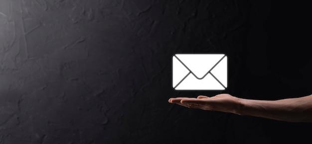 남성의 손이 편지 아이콘, 이메일 아이콘을 들고 있습니다. 뉴스레터 이메일로 문의하고 스팸 메일로부터 개인 정보를 보호하세요. 고객 서비스 콜센터에 문의하십시오. 마케팅 및 뉴스레터를 이메일로 보내주십시오.