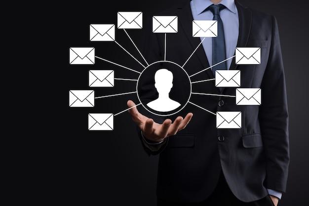 手紙のアイコン、電子メールのアイコンを持っている男性の手。ニュースレターの電子メールで私達に連絡し、スパムメールからあなたの個人情報を保護します。カスタマーサービスのコールセンターにお問い合わせください。メールマーケティングとニュースレター。
