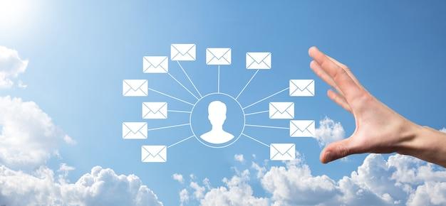 手紙のアイコン、電子メールのアイコンを持っている男性の手。ニュースレターの電子メールで私達に連絡し、スパムメールからあなたの個人情報を保護します。カスタマーサービスのコールセンターにお問い合わせください。メールマーケティングとニュースレター