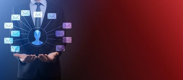 Мужская рука, держащая значок письма, значки электронной почты. свяжитесь с нами по электронной почте информационного бюллетеня и защитите свою личную информацию от спама. контактный центр службы поддержки клиентов свяжитесь с нами.