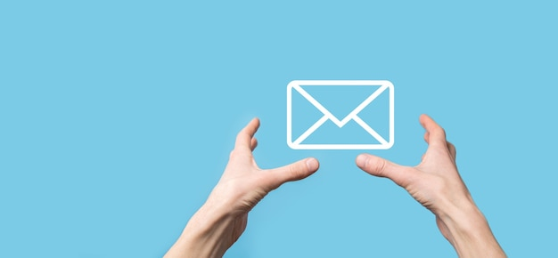 手紙のアイコン、電子メールのアイコンを持っている男性の手。ニュースレターの電子メールでお問い合わせください。スパムメールから個人情報を保護してください。カスタマーサービスのコールセンターにお問い合わせください。メールマーケティングとニュースレター。