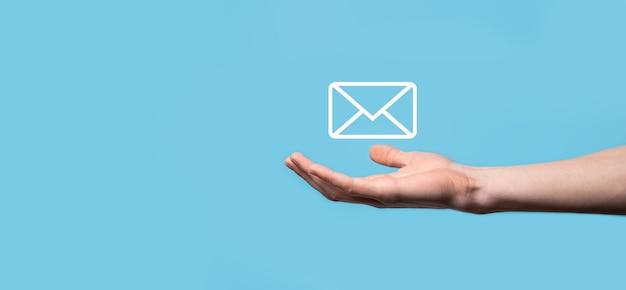 手紙のアイコン、メールのアイコンを持っている男性の手。ニュースレターのメールでお問い合わせいただき、スパムメールから個人情報を保護してください。カスタマー サービス コール センターからお問い合わせください。e メール マーケティングとニュースレター。