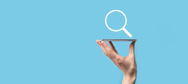 Male hand holding magnifying glass ,search icon on blue background. concept search engine optimization, customer support.browsing internet data information.networking concept.