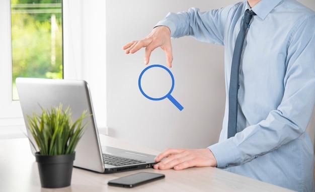 돋보기, 검색 아이콘을 들고 남성 손입니다. 개념 검색 엔진 최적화