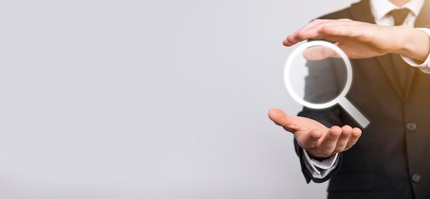 Мужская рука держит увеличительное стекло, значок поиска на синем фоне. концепция поисковой оптимизации, поддержка клиентов. просмотр информации в интернете. концепция сети.