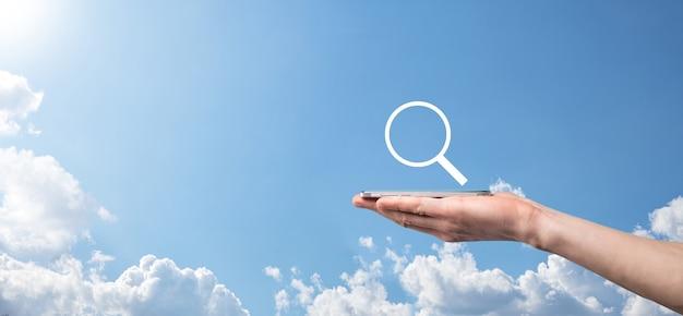 虫眼鏡を持っている男性の手、青い背景の上の検索アイコン。コンセプト検索エンジン最適化、カスタマーサポート。インターネットデータ情報の閲覧。ネットワーキングコンセプト。