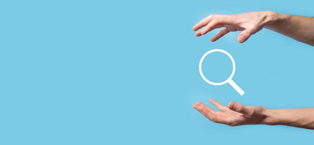 虫眼鏡を持っている男性の手、青い表面の検索アイコン。コンセプト検索エンジン最適化、カスタマーサポート