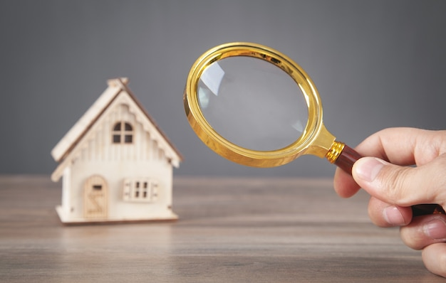 Male hand holding magnifying glass with a house model. real estate. inspection