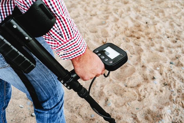 地上で金属探知機を持っている男性の手