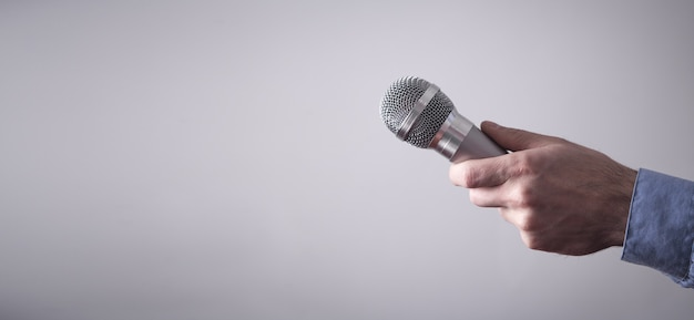Male hand holding microphone on gray background.