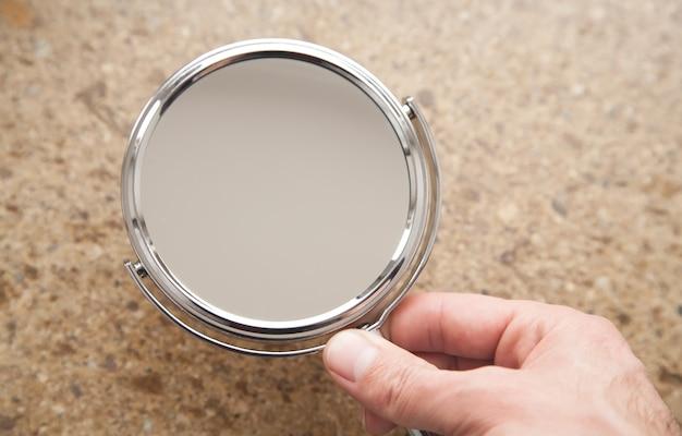 Мужская рука держит зеркало на коричневом фоне.