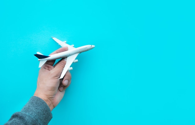 Male hand holding model plane,airplane on blue pastel color background.