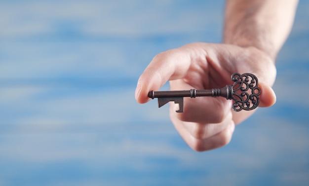 古い鍵を持っている男性の手。仕事。成功