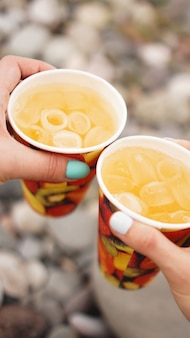 돌, 자갈 해변의 배경에 레모네이드와 종이 컵을 들고 남성 손. 해변 휴가 개념