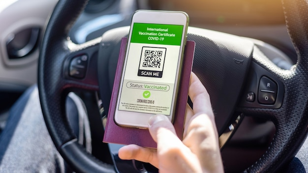 Passaporto maschile e smartphone con certificato di vaccinazione internazionale covid-19 codice qr in un'auto