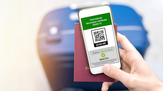 Male hand holding passport and smartphone with international vaccination certificate covid-19 qr code, suitcase