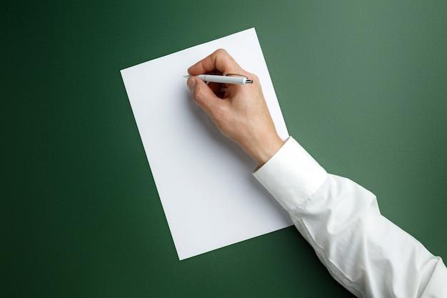 남성 손 펜을 들고 텍스트 또는 디자인에 대 한 녹색 벽에 빈 시트에 쓰기. 연락처, 광고 또는 비즈니스 사용을위한 빈 템플릿. 금융, 사무실, 구매. copyspace.