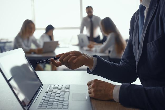Мужской рукой, держащей перо указывая экран компьютера. бизнесмен, работающий на ноутбуке в современном офисе