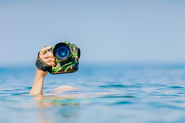 Male hand holding photocamera above water in sea.
