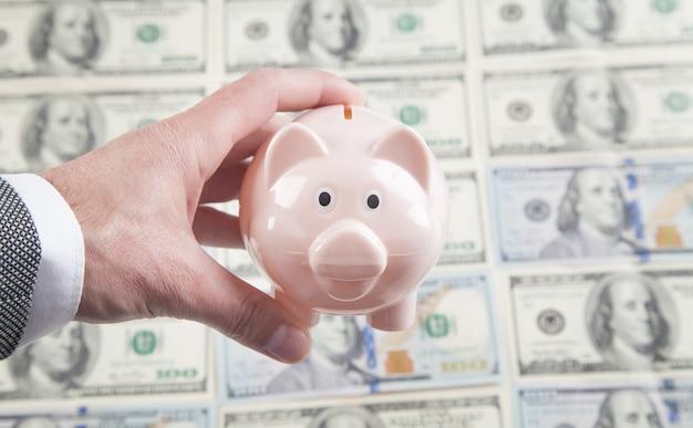 Мужская рука, держащая копилку на инвестиции долларовых банкнот
