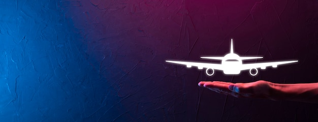 Male hand holding plane airplane icon on blue background. banner.nline ticket purchase.travel icons about travel planning, transportation, hotel, flight and passport.flight ticket booking concept.