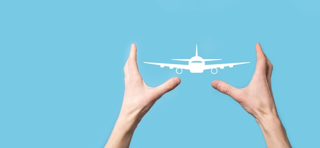 Male hand holding plane airplane icon on blue background.