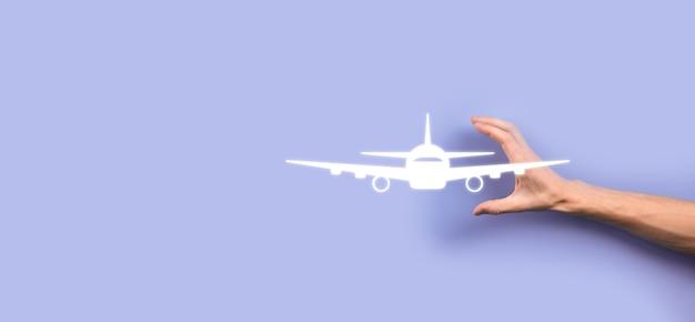 青い背景の上の飛行機の飛行機のアイコンを持っている男性の手。 banner.nlineチケット購入。旅行計画、交通機関、ホテル、フライト、パスポートに関する旅行アイコン。フライトチケット予約のコンセプト。