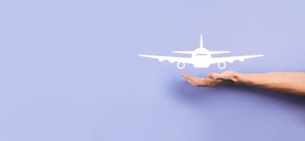파란색 배경에 비행기 비행기 아이콘을 들고 남성 손. banner.nline 티켓 구매입니다. 여행 계획, 교통, 호텔, 항공편 및 여권에 대한 여행 아이콘입니다. 항공권 예약 개념입니다.