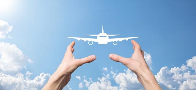 Мужская рука, держащая значок самолета на синем фоне. banner.nline покупка билета. путешествие значки о планировании путешествия, транспорте, отеле, рейсе и паспорте. концепция бронирования авиабилетов.