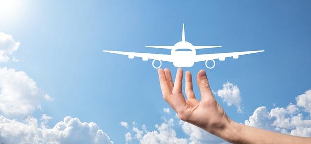 파란색 배경에 비행기 비행기 아이콘을 들고 남자 손. banner.nline 티켓 구매. 여행 계획, 교통, 호텔, 항공편 및 여권에 대한 여행 아이콘. 비행 티켓 예약 개념.