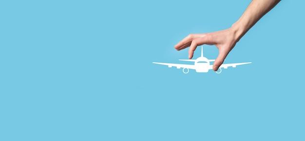 青い背景に飛行機の飛行機のアイコンを持っている男性の手。nlineチケットの購入。旅行計画、交通機関、ホテル、フライト、パスポートに関する旅行アイコン。フライトチケット予約のコンセプト。