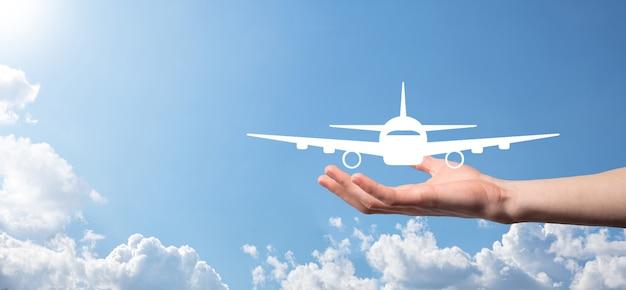 Мужская рука, держащая значок самолета на синей поверхности. покупка билетов banner.nline