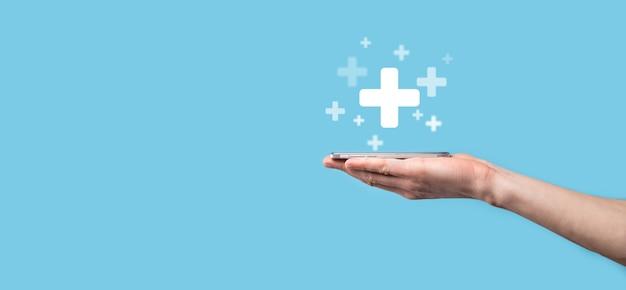 남자 손 잡고 플러스 파란색 배경에 아이콘입니다. 더하기 기호 가상은 혜택, 개인 개발, 소셜 네트워크 이익, 건강 보험, 성장 개념과 같은 긍정적 인 것을 제공하는 것을 의미합니다.