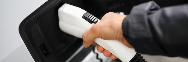 Мужская рука держит разъем зонда автомобильной зарядной станции