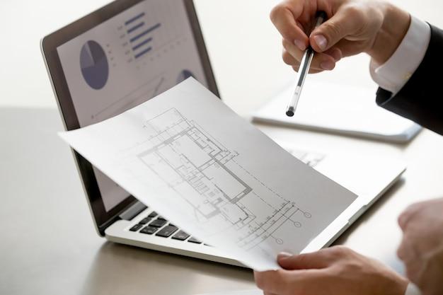 Мужской рукой, держащей план проекта, статистика на экране, крупным планом