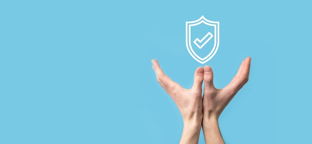 Мужская рука защищает щит со значком галочки на синем фоне. компьютер безопасности сети защиты и безопасное понятие данных.