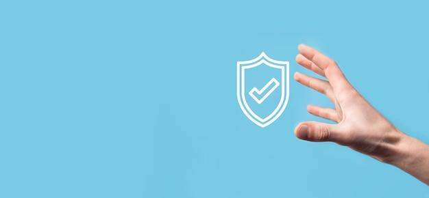 青の背景にチェック マーク アイコンが付いた保護シールドを持っている男性の手。保護ネットワーク セキュリティ コンピューターと安全なデータの概念。
