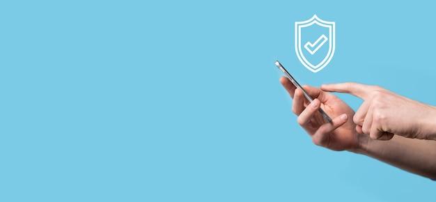 남성 손 잡고 보호 방패 파란색 배경에 확인 표시 아이콘. 네트워크 보안 컴퓨터를 보호하고 데이터 개념을 안전하게 보호합니다.