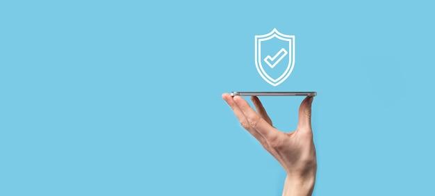 青い表面にチェックマークアイコンが付いている保護シールドを持っている男性の手