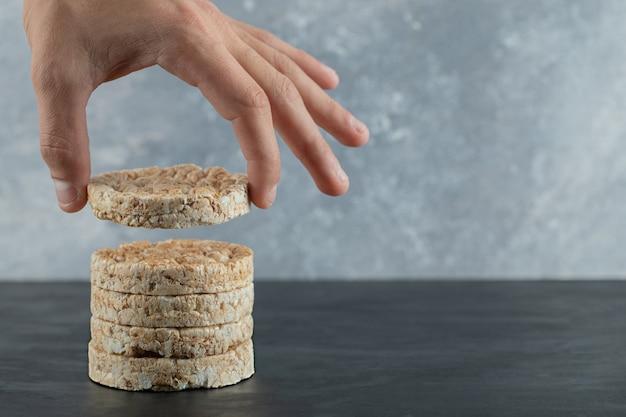 Mano maschio che tiene la torta di riso soffiato sulla superficie di marmo