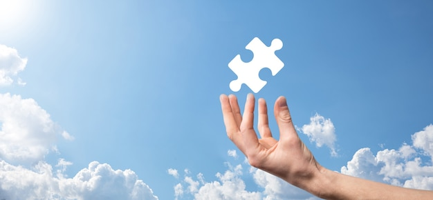 Male hand holding puzzle icon on blue background. pieces representing the merging of two companies or joint venture, partnership, mergers and acquisition concept.