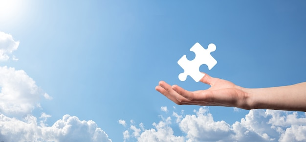 Male hand holding puzzle icon on blue background. pieces representing the merging of two companies