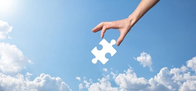 파란색 배경에 퍼즐 아이콘을 들고 남성 손입니다. 두 회사 또는 합작 투자, 파트너십, 합병 및 인수 개념의 합병을 나타내는 조각.
