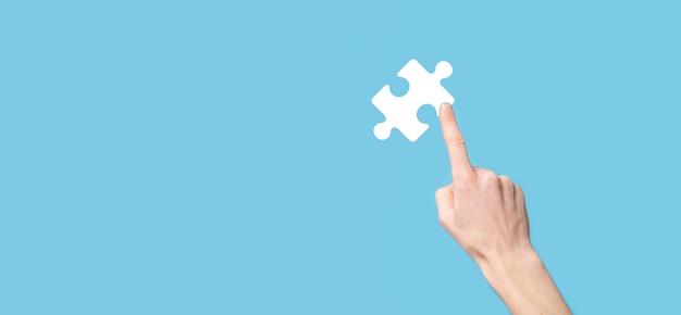 青い背景にパズルアイコンを持っている男性の手。 2つの会社の合併または合弁事業、パートナーシップ、合併および買収の概念を表す作品。