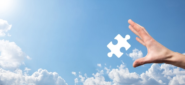 青い背景の上のパズルアイコンを持っている男性の手。 2つの会社の合併または合弁事業、パートナーシップ、合併および買収の概念を表す作品。