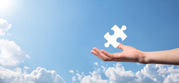 Мужской рукой, держащей значок головоломки на синем фоне. части, представляющие слияние двух компаний